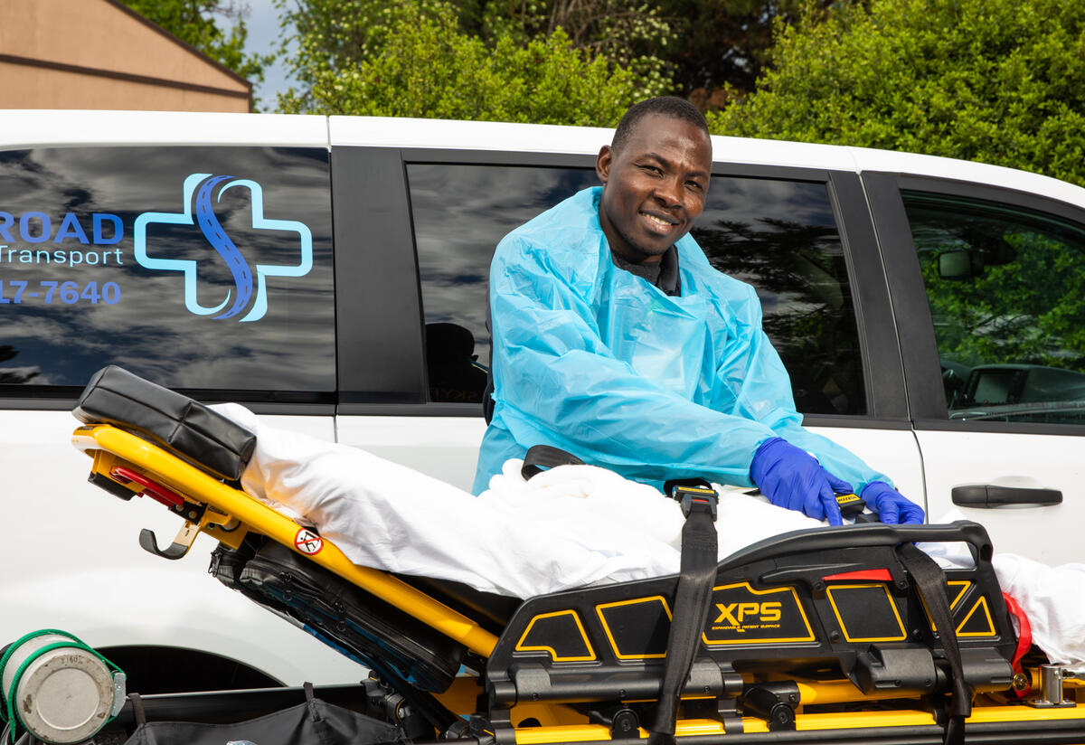 Jonathan Amissa, wearing scrubs, stands in front of a van with his hands on a stretcher. The van has a logo for Skyroad Medical Transport, his medical transportation business.