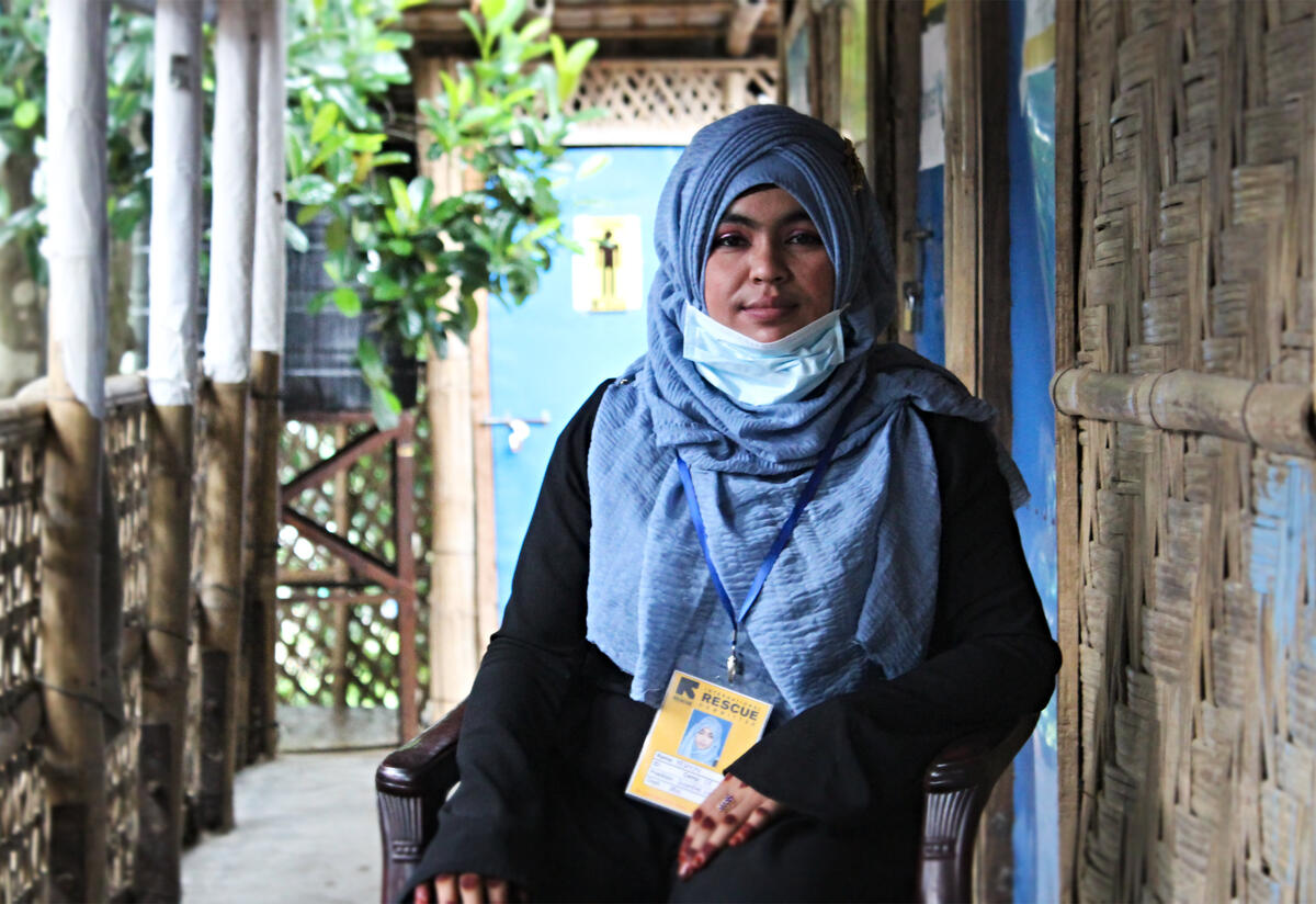 Yasmin sits on a chair on a porch in Cox's Bazar, Bangladesh. She is wearing an IRC lanyard and ID.
