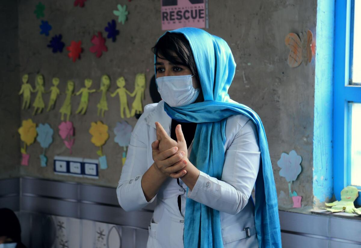 Sohalia Khaliqi stands in a class room demonstrating proper handwashing techniques. She is wearing a bright blue headscarf and white mask. Behind her, the wall is decorated with childrens artwork.