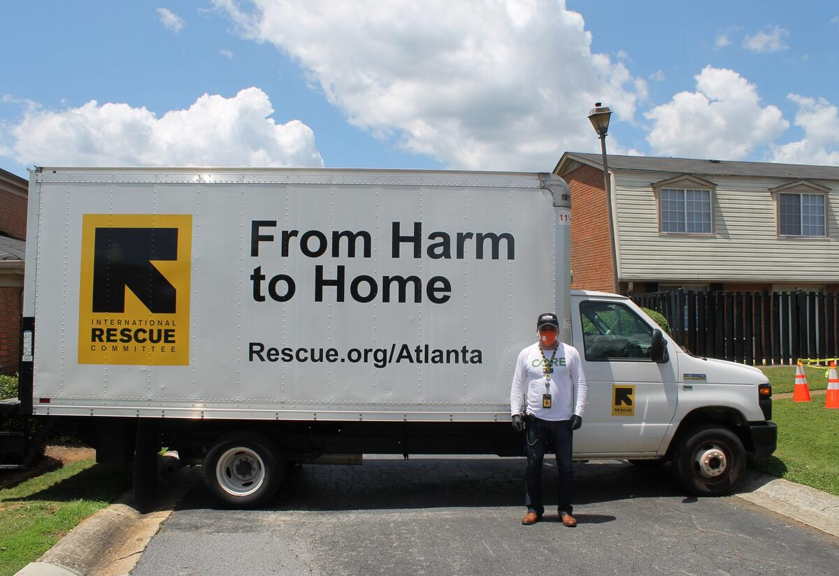 """A man wearing an N-9 respirator mask and black medical gloves stands in front of a large truck with the IRC logo which reads """"International Rescue Committee"""" and the phrase """"From Harm to Home"""" on the side."""