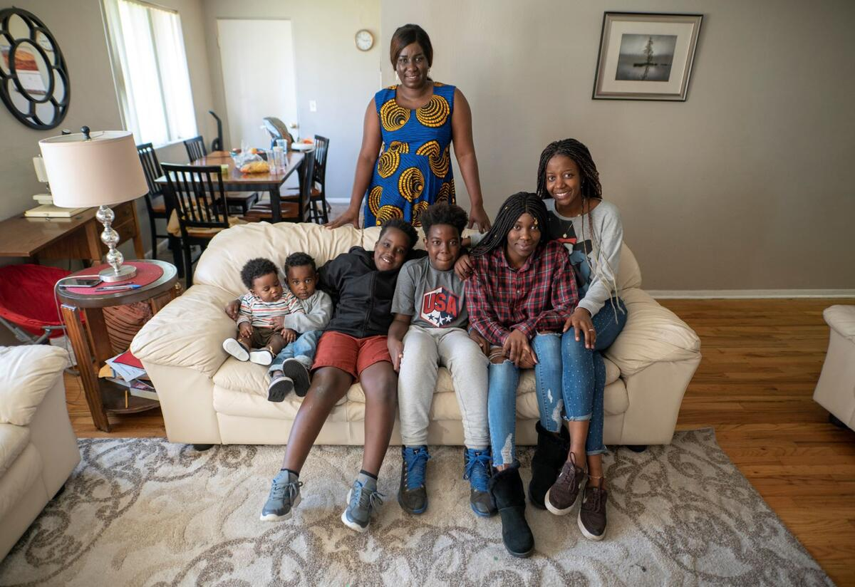 Jacqueline Uwumeremyi stands behind a couch where all of her children sit. There are 6 children, 4 boys and 2 girls.