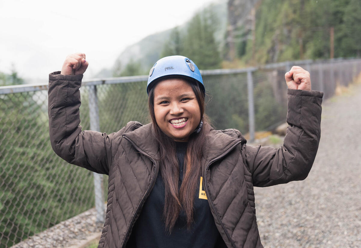 Close-up photo of smiling teenage girl with arms up in a strong pose. Girl wears winter coat and rock climbing helmet, and is outdoors in wooded area.