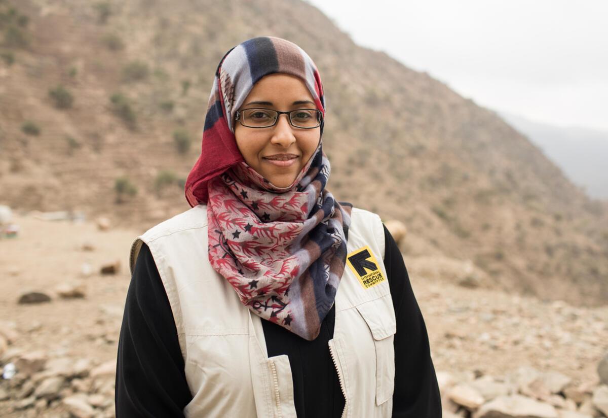 Dr Rasha Rashed, wearing an IRC vest, stands outside in front of a desert landscape