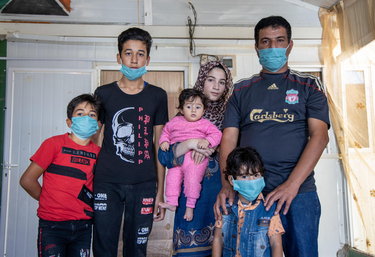 In a small tin home in a refugee camp, Manhal poses with his family: his wife holds a baby in a pink onesie, his four-year-old stands in front of him and eight-year-old and fifteen-year-old sons stands next to them.