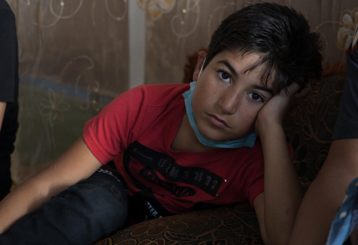Nine-year-old Ahmad sits and looks at the camera with his head in his hand.