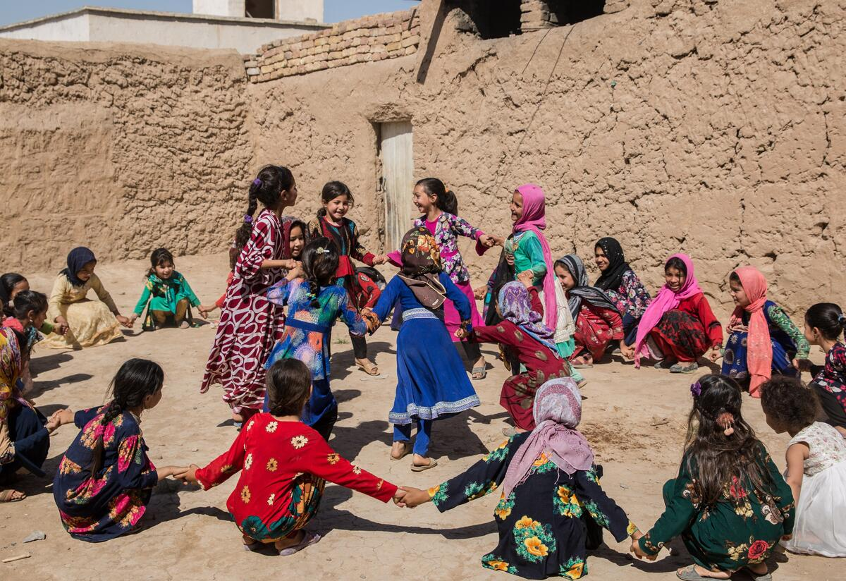 Young schoolgirls in Afghanistan hold hands sitting in a ring around a group of classmaters who are dancing.