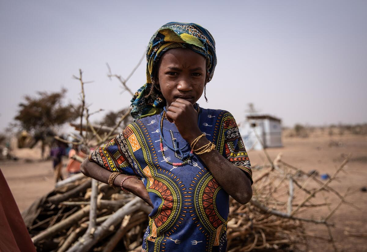 A young girl poses for a portrait in camp for internally displaced people in Barsalogho, Burkina Faso.