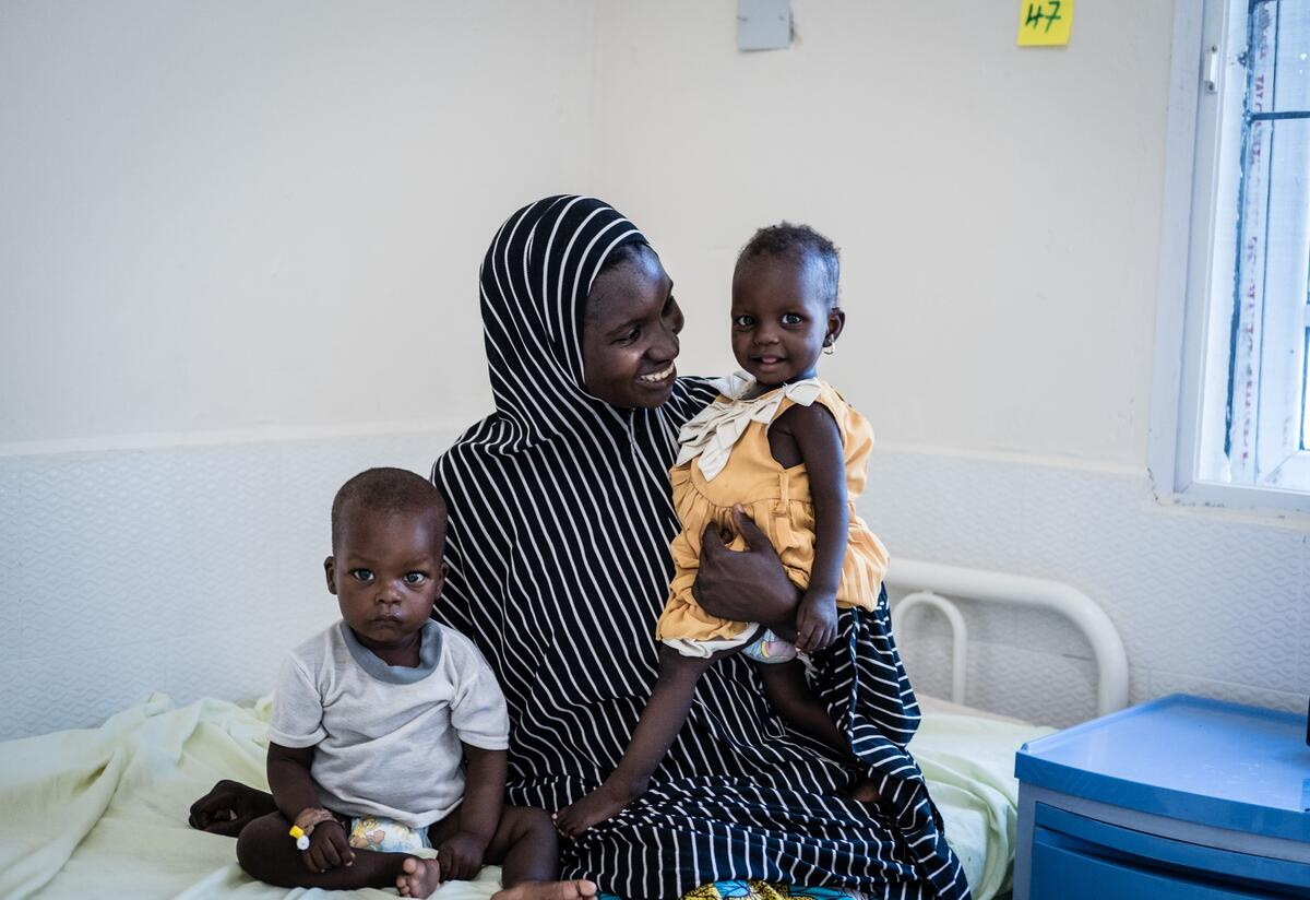 A mother sits on a hospital bed with her two young children in the Nigeria health center where they were being treated for acute malnutrition,