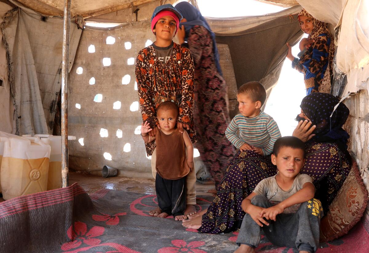 A family sits inside their tent in Syria after being displaced by violence.