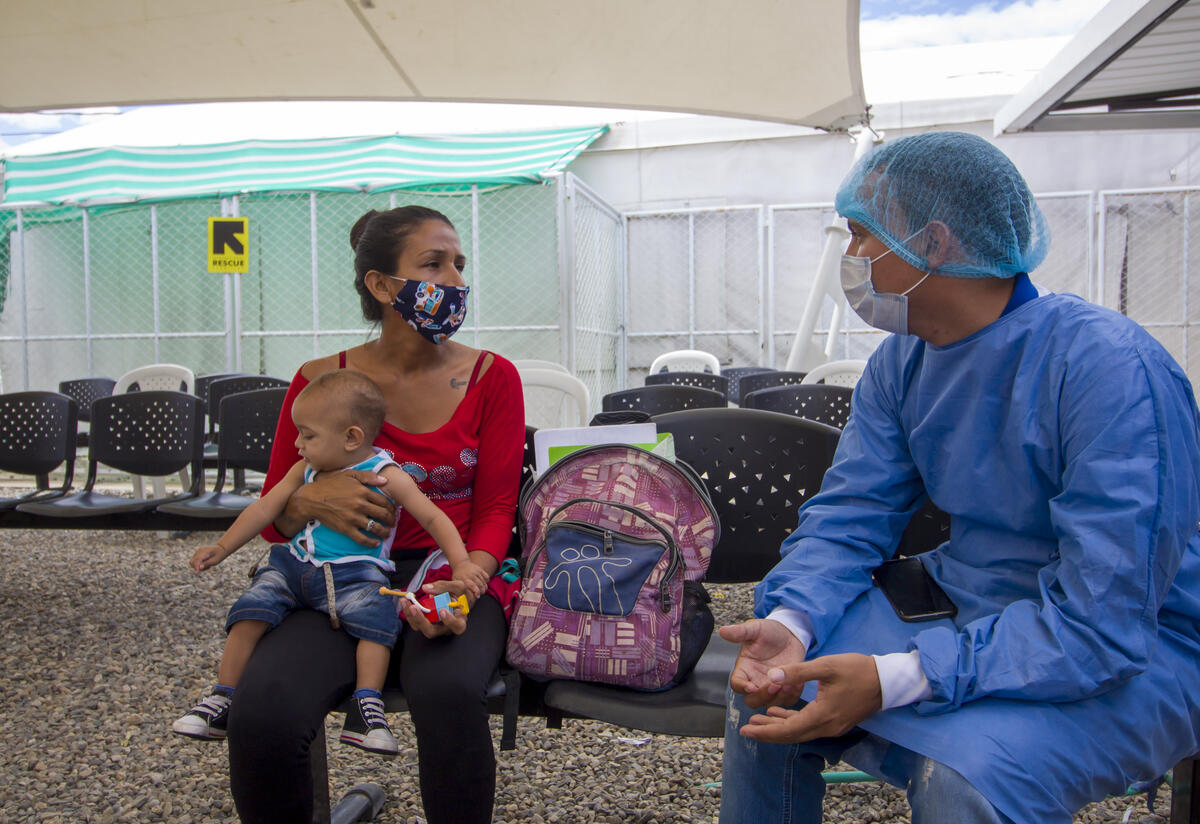 A health worker speaks with a mother holding her baby at a migrant center on the Colombian border with Venezuela, where the IRC is providing medical services.