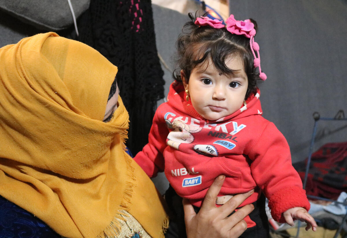 Um Tamer cradles her daughter Zainab in her tent in Areesha refugee camp in Syria.