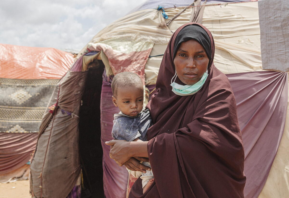Amina stands in front of tents outside while holding their son.