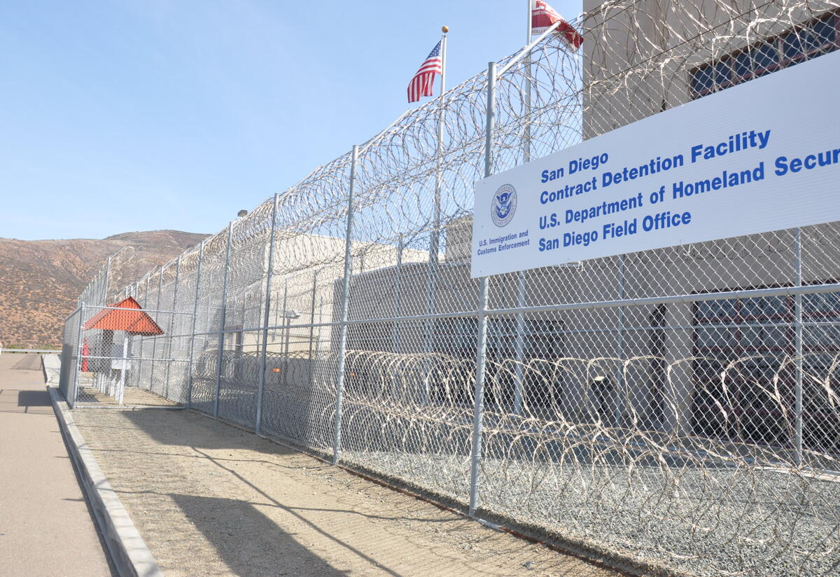 An immigrant detention center. There is a barbed wire fence and a sign that says San Diego Contract Detention Facility.