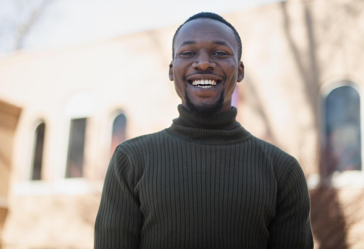Fredrick Shema, outside and wearing a green sweater, smiles.