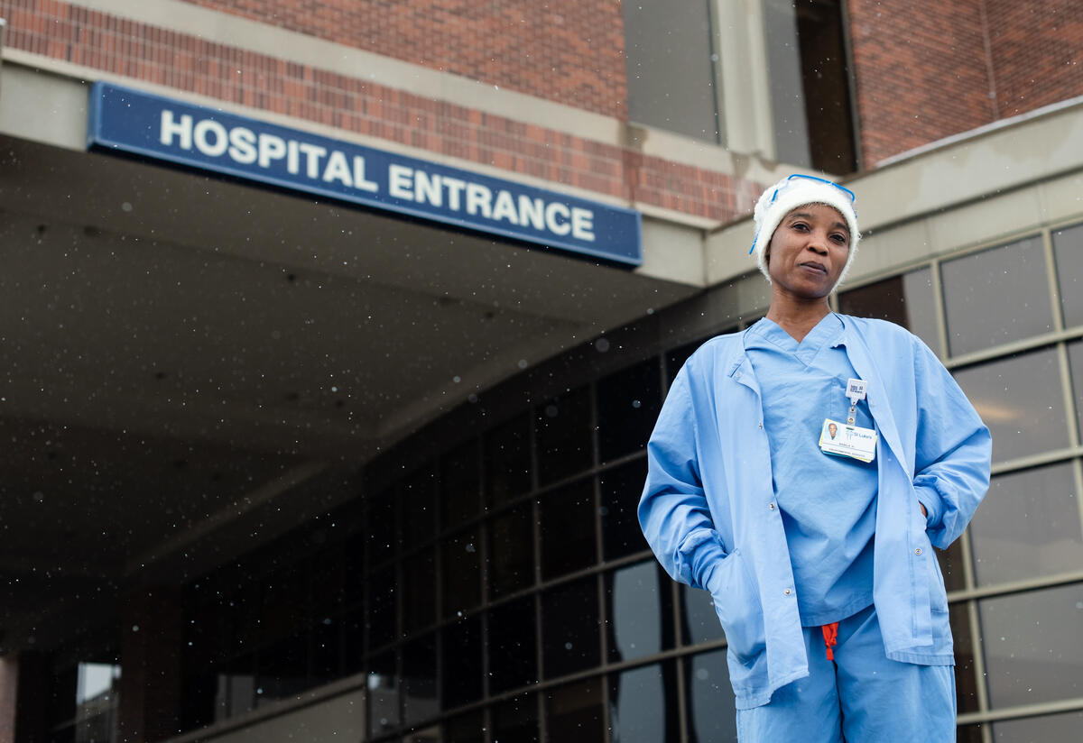 Nabila in front of the hospital where she works. She is wearing blue scrubs.
