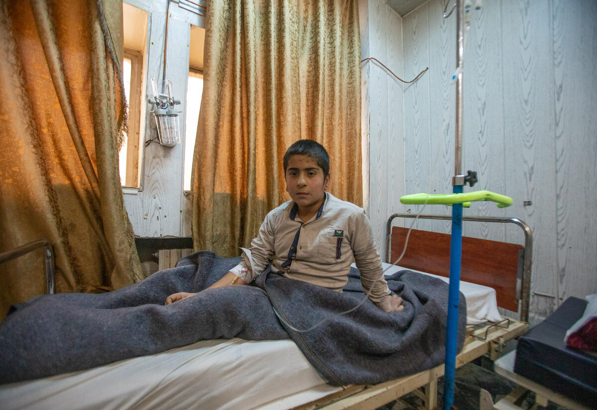 A boy sits up in his hospital bed in Syria.