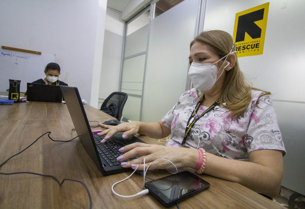 An IRC health worker in Colombia, wearing a mask to prevent the spread of COVID 19, types at her laptop in an IRC office.