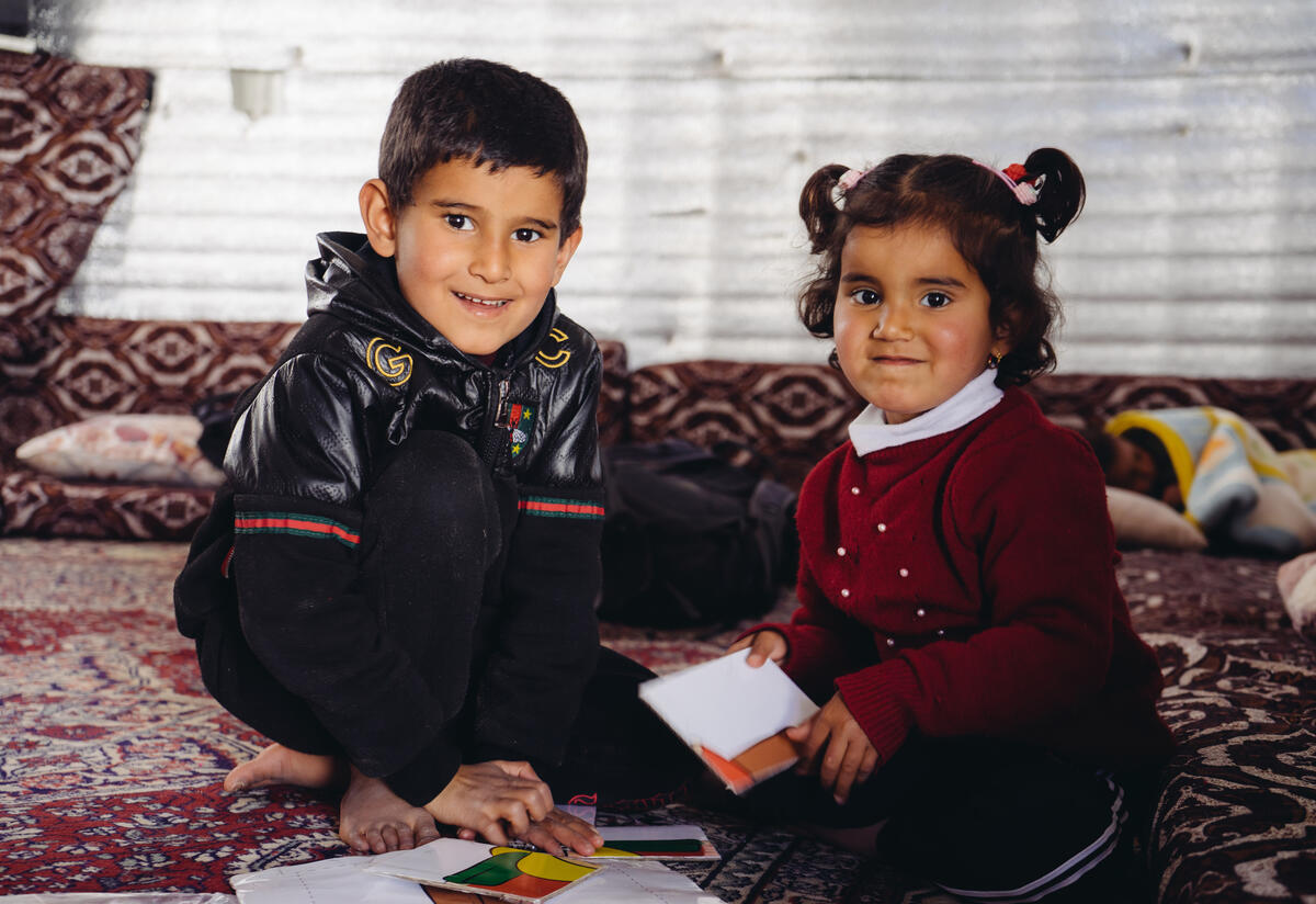 5-year-old Syrian boy Ayham and his 3-year-old sister Reham sit on a mat playing with a puzzle.
