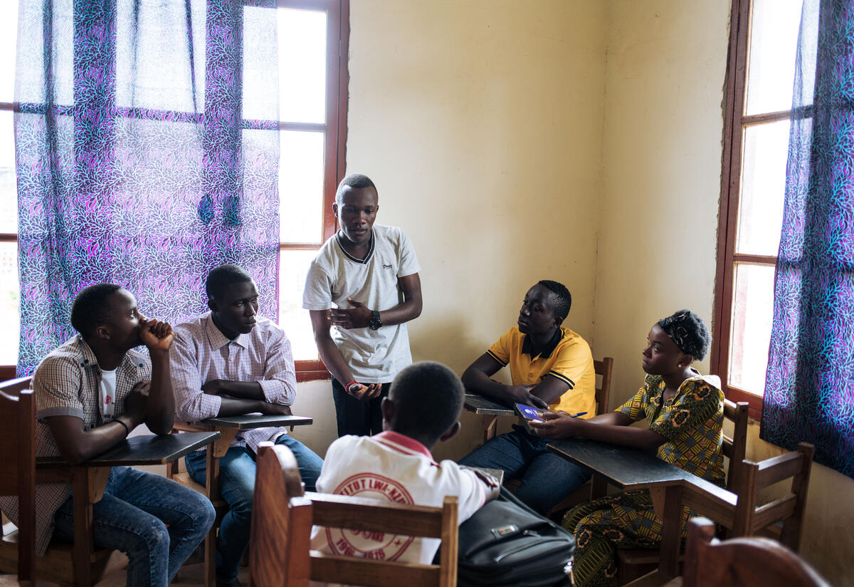 Benjamin, standing in a classroom in Congo, speaks to other teenagers seated at desks around him about Ebola.