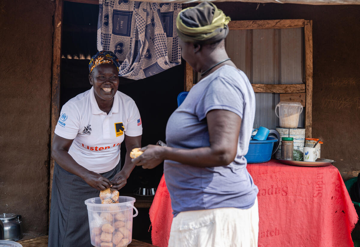 South Sudanese refugee Jemimah Sadia, holding a plastic bag of small cakes, speaks with a customer at her small tea shop in a Ugandan refugee camp.olding a