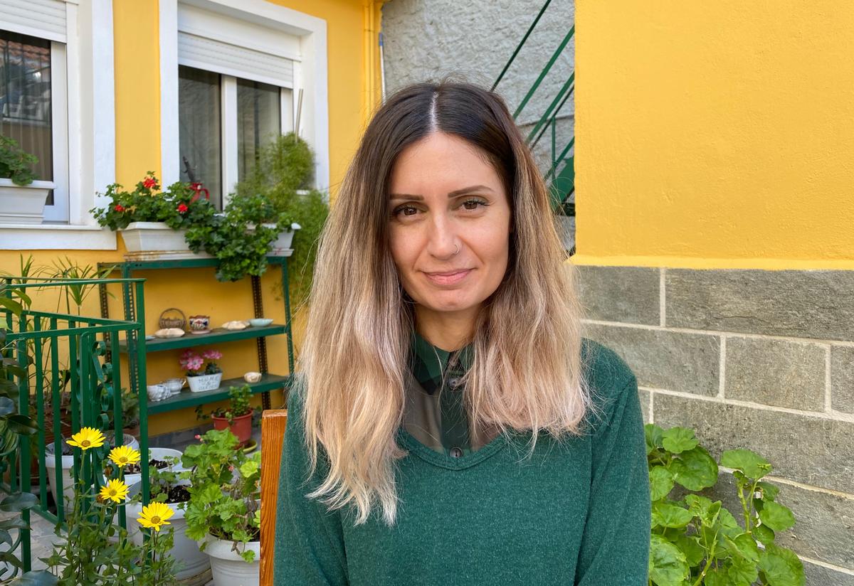 Kiki Michailidou, wearing a green sweater, sits outside a yellow house near a garden