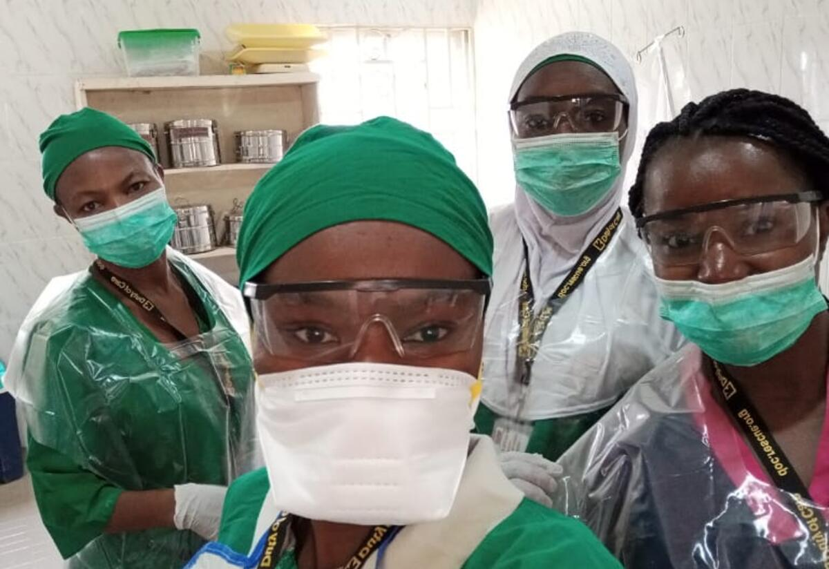 Wearing green scrubs, masks and face shields, midwives in an IRC reproductive health clinic take a selfie