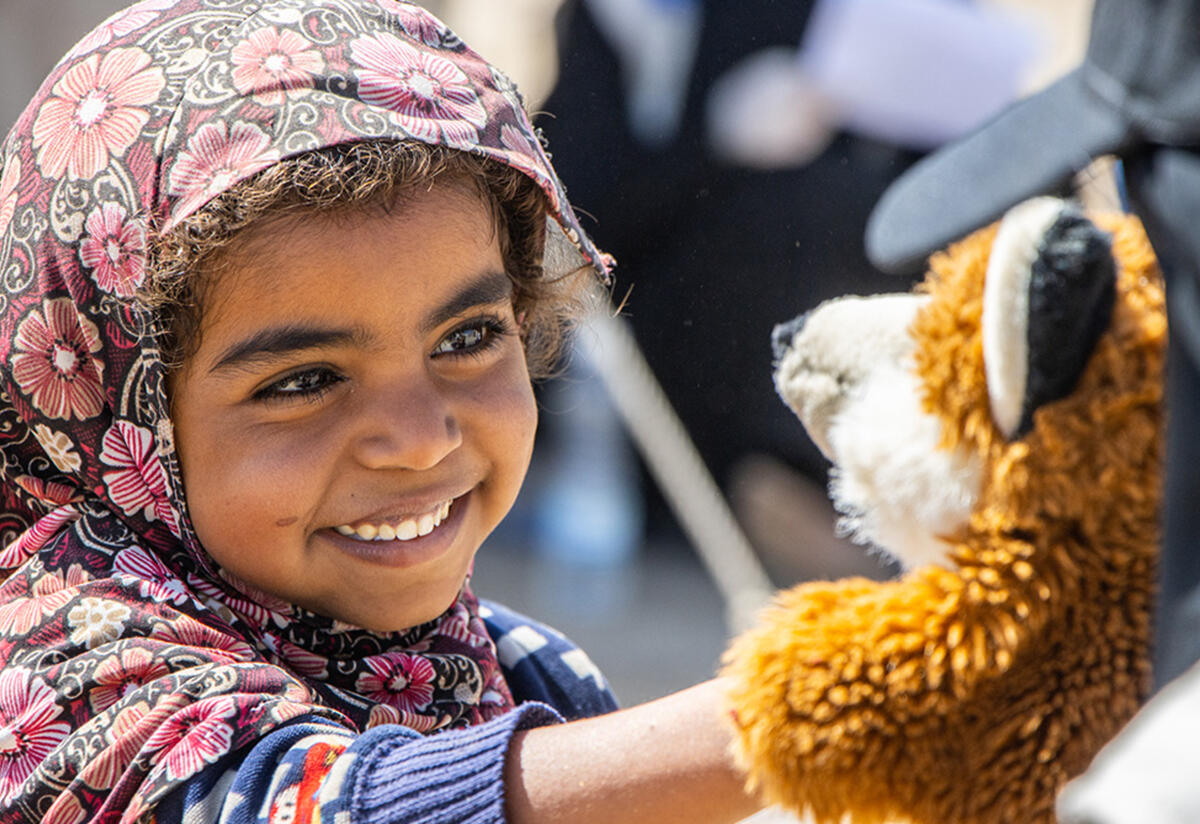 Najeeba smiles while she reaches out to touch a fox puppet