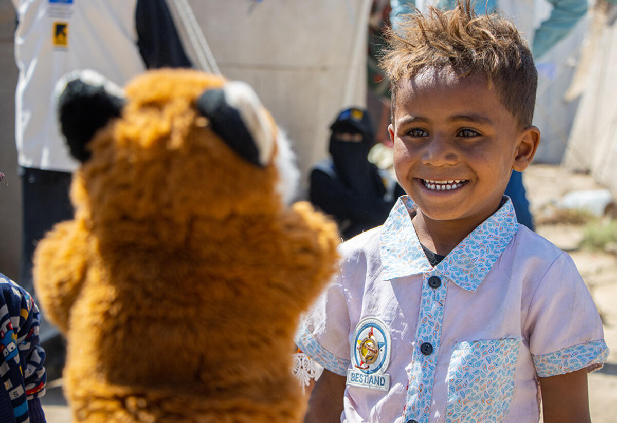 Outside in Al-Manshar camp, five-year-old Yasser laughs while looking at a fox puppet
