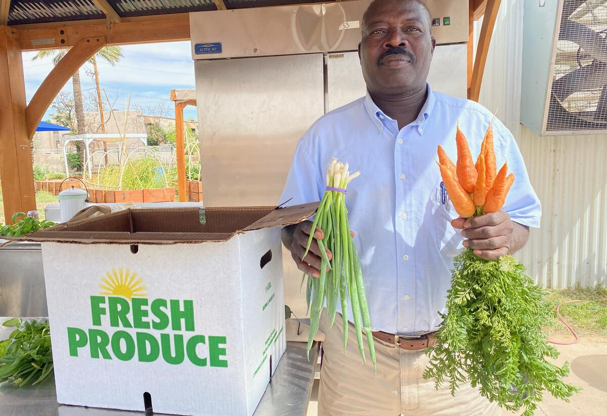 Abdelgabar Mohamdian shows carrots and green onions that he grows and sells.