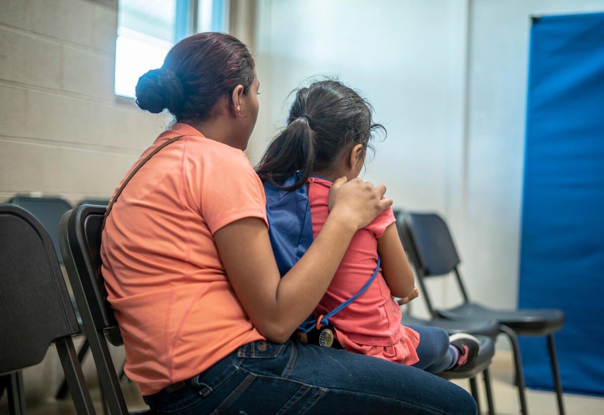 In an IRC shelter, a young mother sits with her back to the camera and her arm around her 4-year-old daughter.