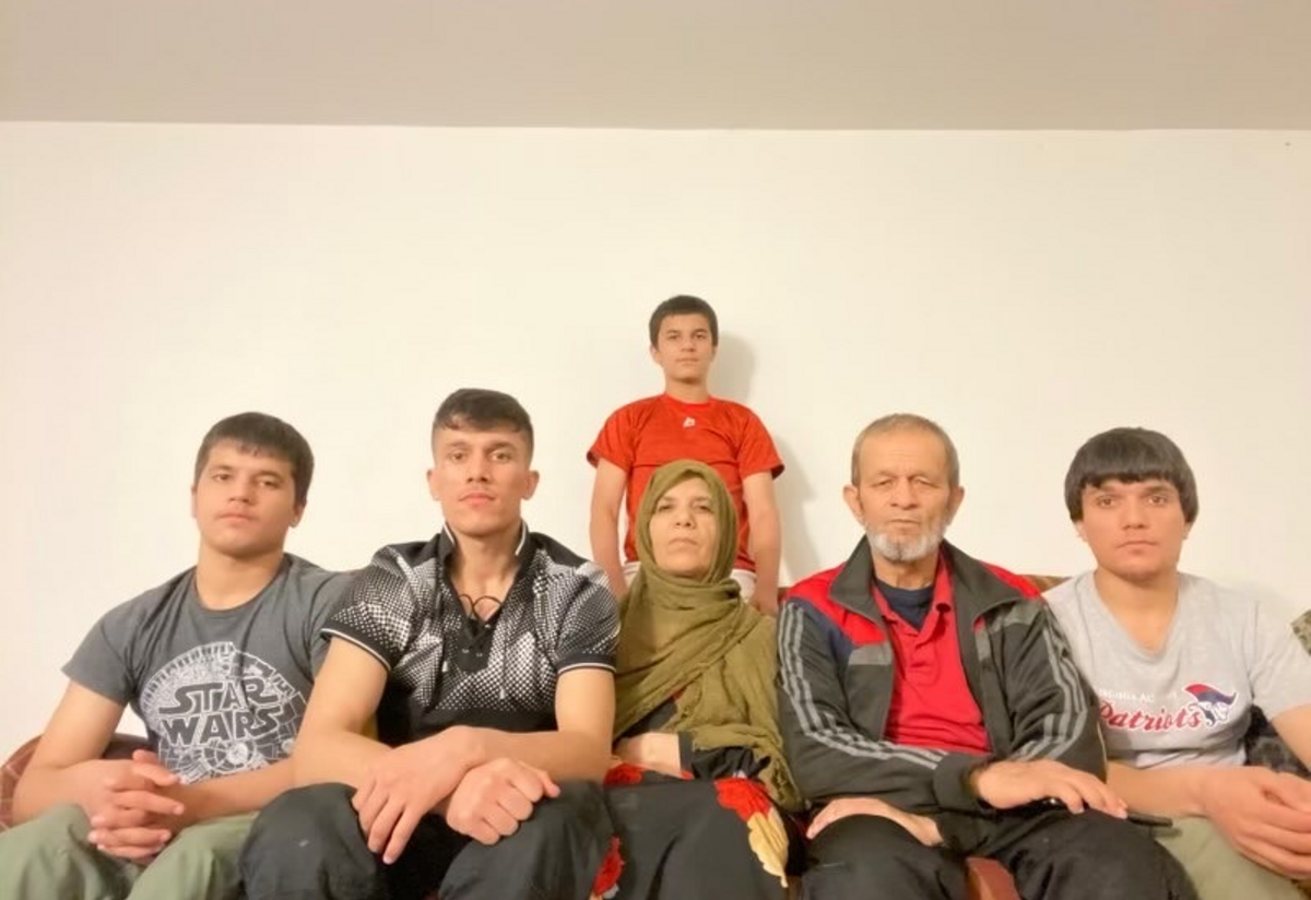 Mohammad and Nazifah sit on the couch, surrounded by thier four boys.