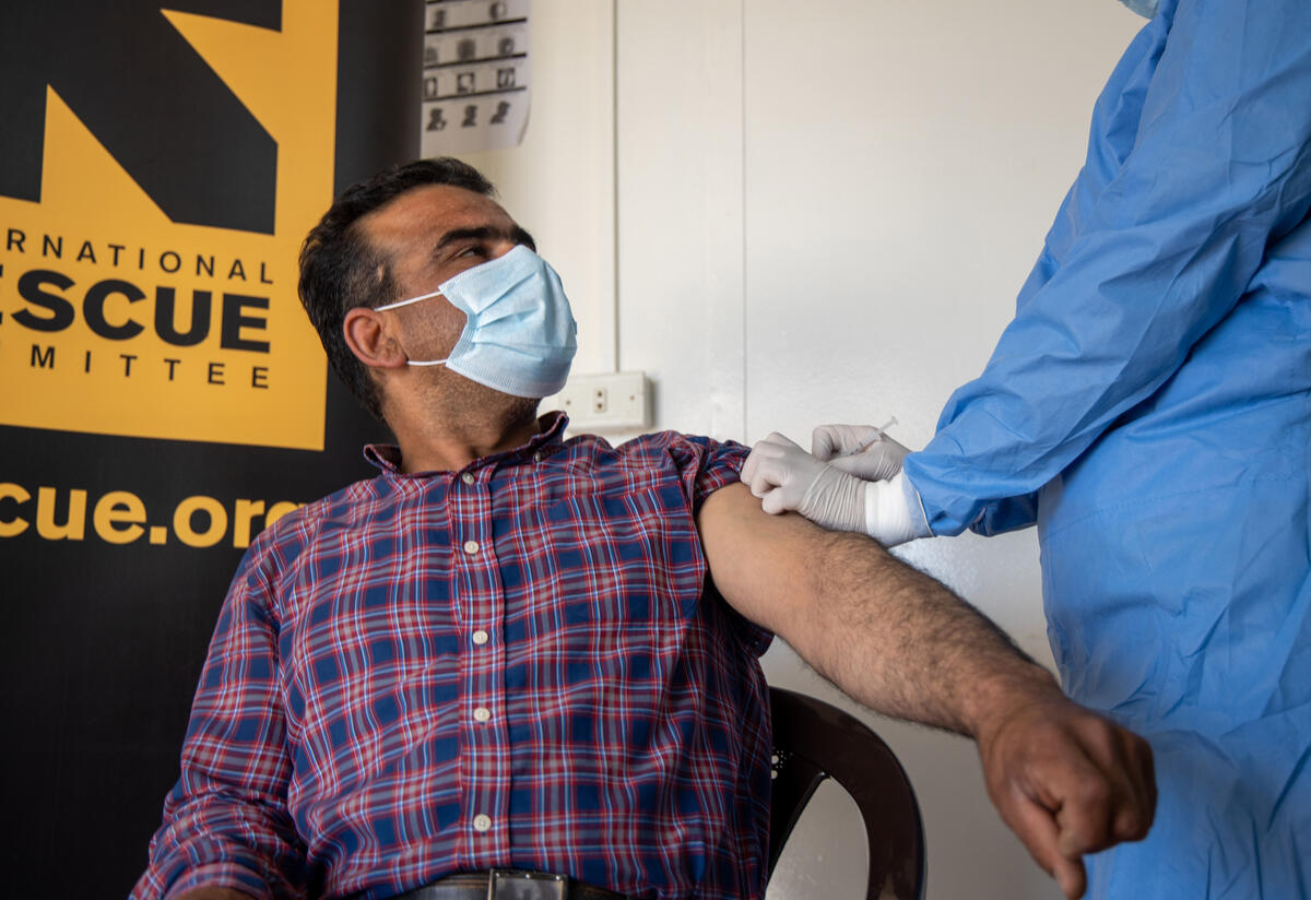A Syrian man sitting with his sleeve rolled up receives a COVID-19 vaccination from a nurse at an IRC clinic in Zaatari refugee camp in Jordan