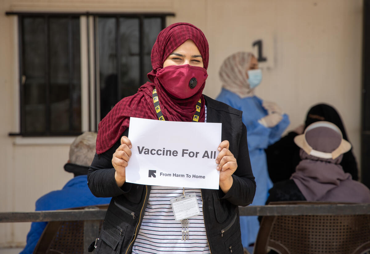 """An IRC senior health officer wearing a face mask against COVID-19 stands holding a """"Vaccines for All"""" sign at the IRC health clinic where she works in Zaatari refugee camp in Jordan"""