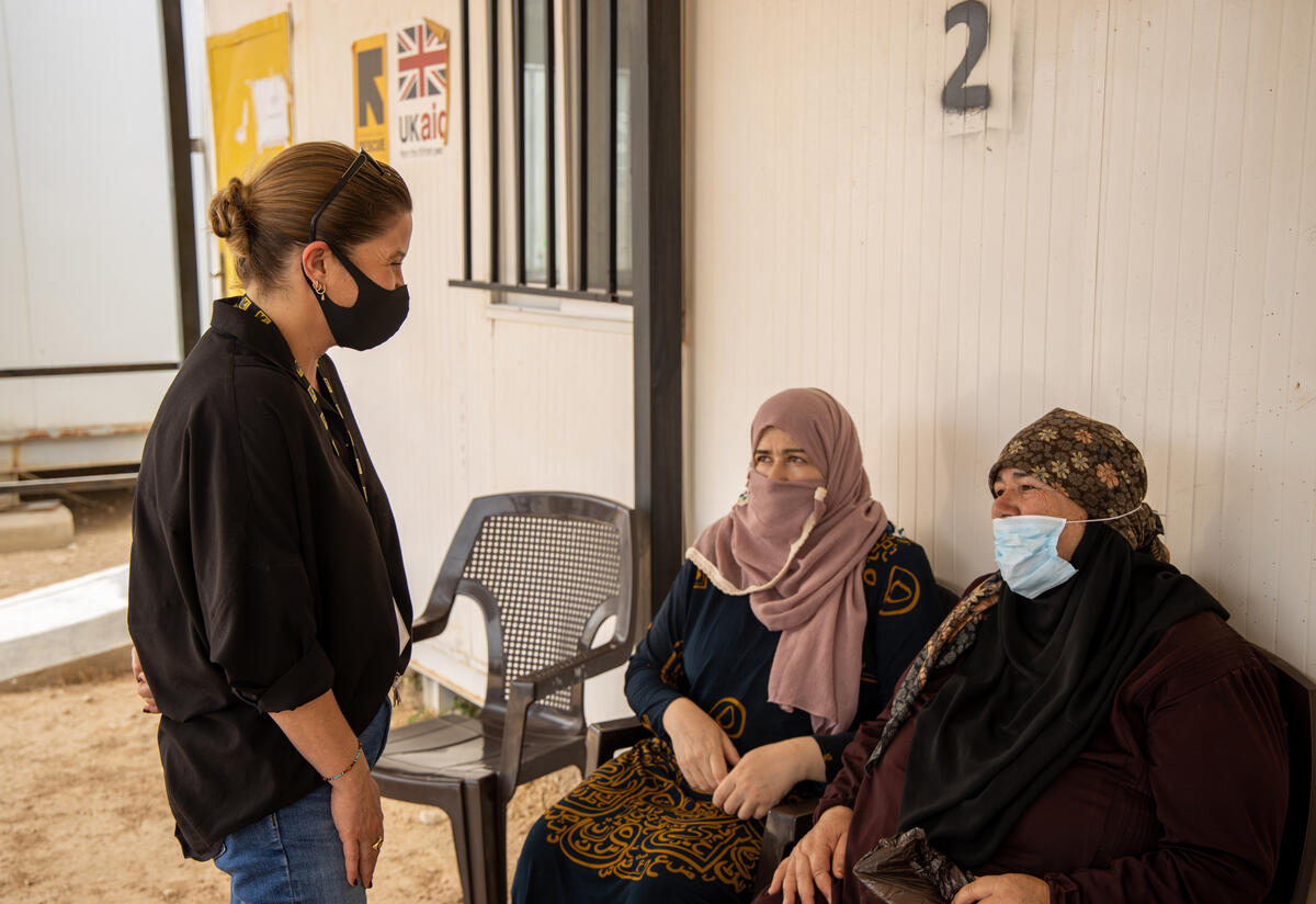 Sarra Ghazzi, IRC country director in Jordan stands speaking with two seated Syrian women waiting to get COVID-19 vaccinations at an IRC clinic.