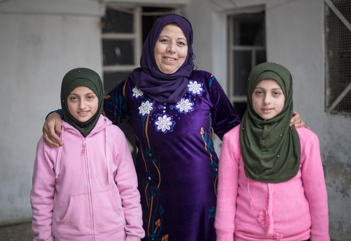 Reema stands between her twins Shurouq and Shirina with her arms around them.