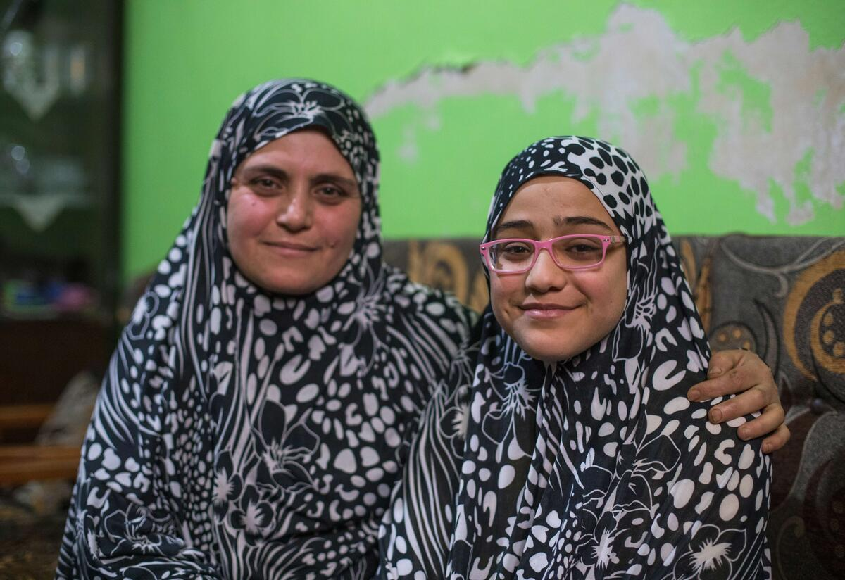 Wearing matching outfits, Ruba and her daughter Salam sit next to one another.
