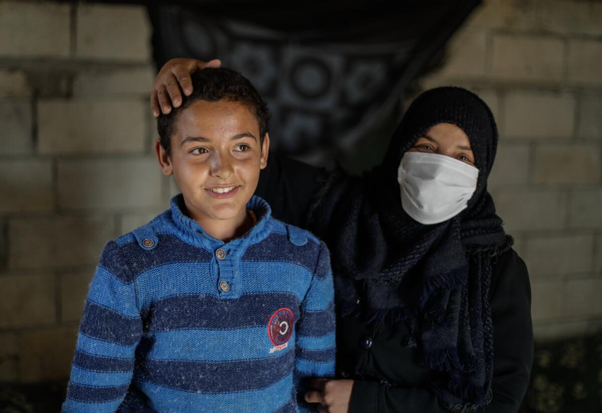 Muna stands next to her son Tareq with her hand on his head.