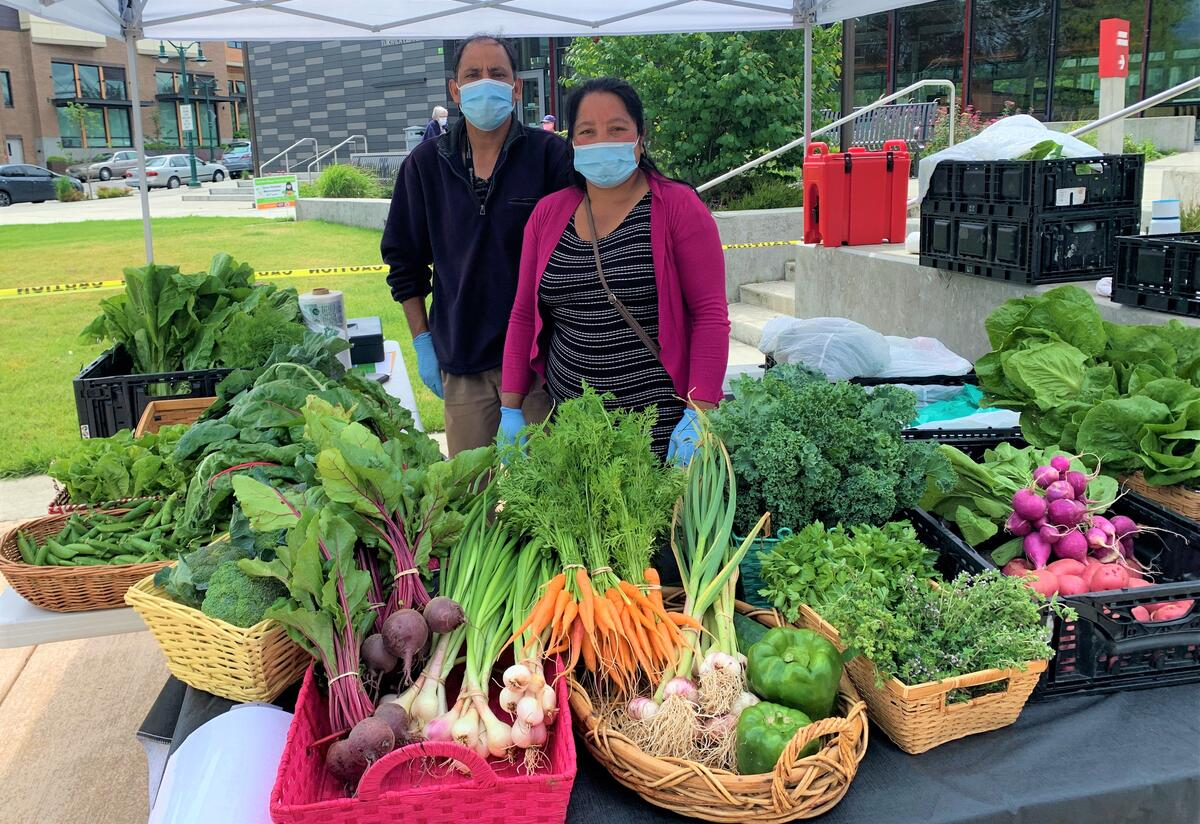 Two farmers wearing face masks stand behind a table full of fresh, locally grown vegetables and herbs in baskets.