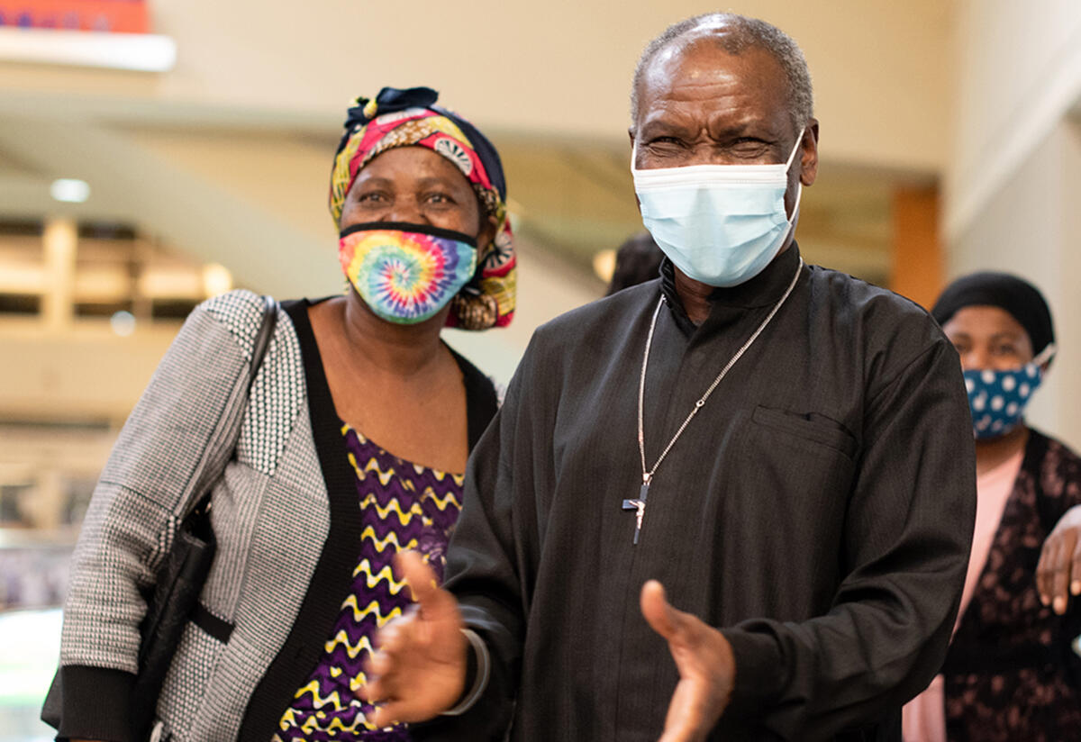 Patrice and Wanyema, both wearing masks, both watch their daughter arrive at the Boise airport. Patrice is about to clap his hands.