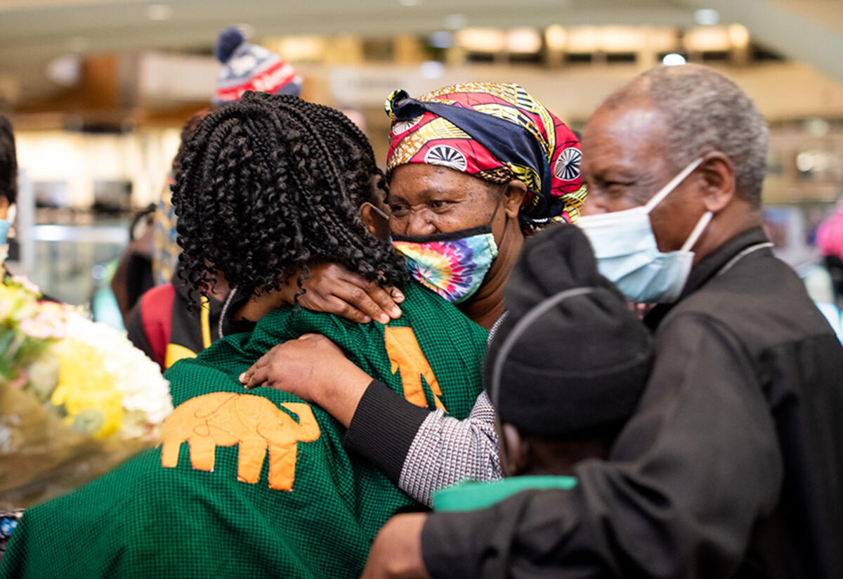 Mauwa hugs her mother while her father, son and other family members stand nearby in the airport.