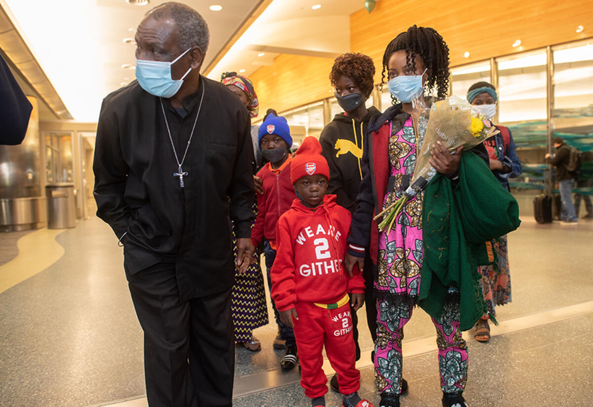 Patrice, Mauwa and family after they arrived at the airport stand in the airport. Mauwa is holdin g