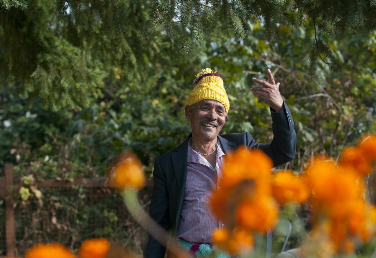 Elder Nepali man dances at IRC community garden.