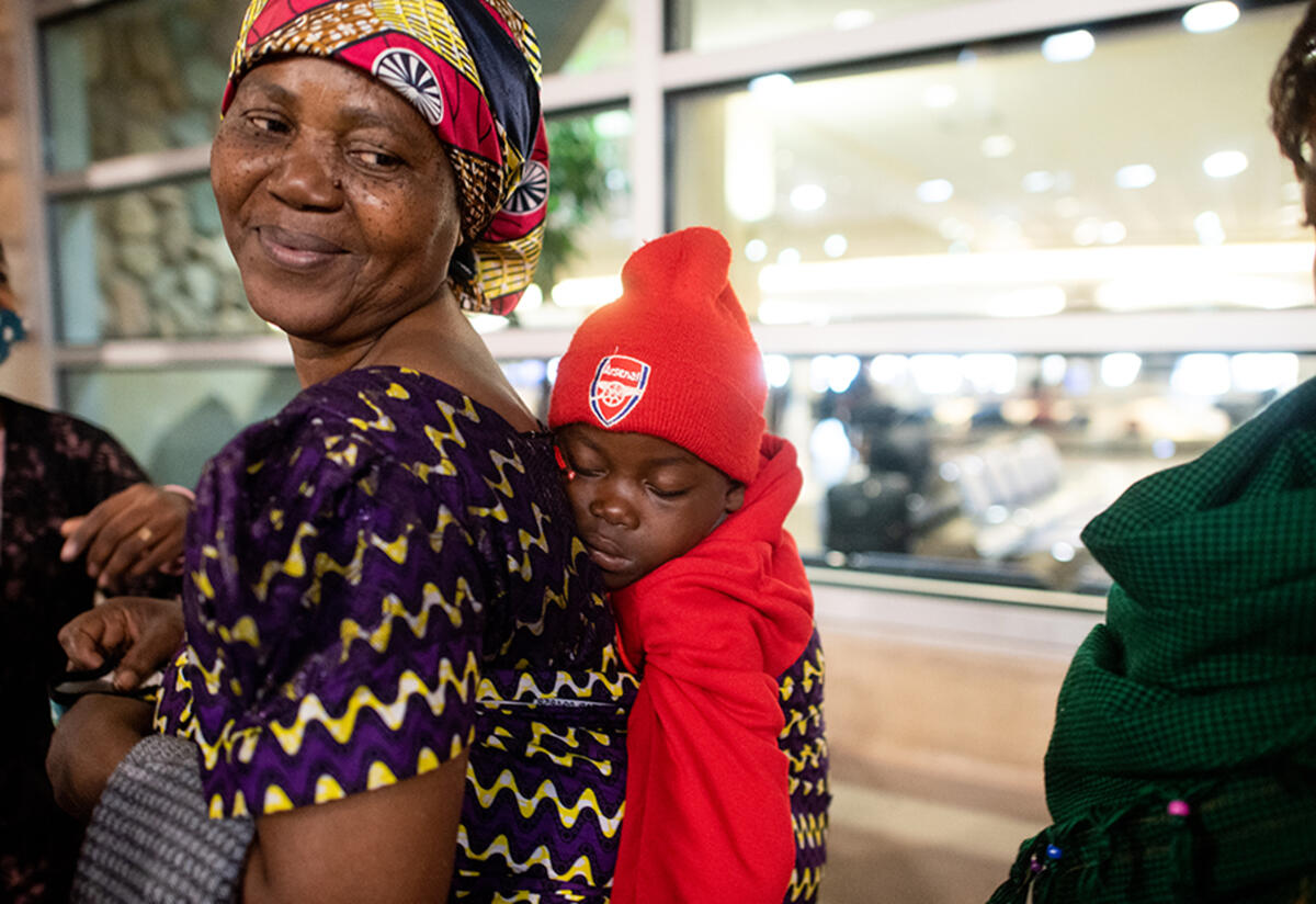 Wanyema smiles with a baby on her back at the Boise Airport