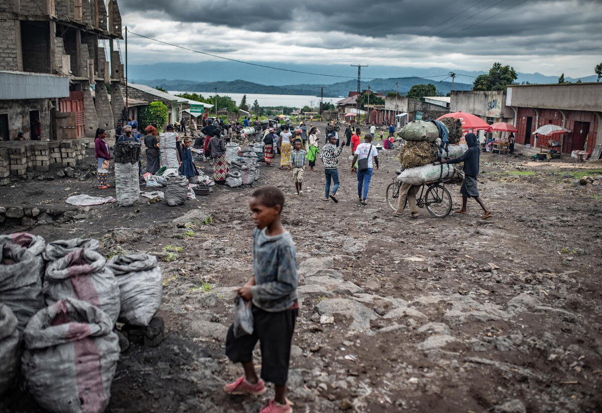 A young boy and other people on the streets of Goma under a cloudy sky with mountains and a lake in the background.
