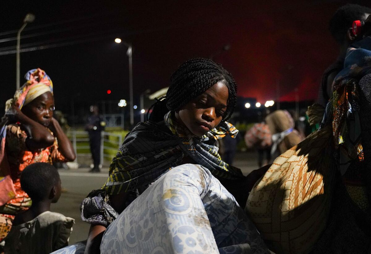 A young woman carries a mattress and other belongings as people flee to Rwanda after the Nyiragongo volcano erupted near Goma.