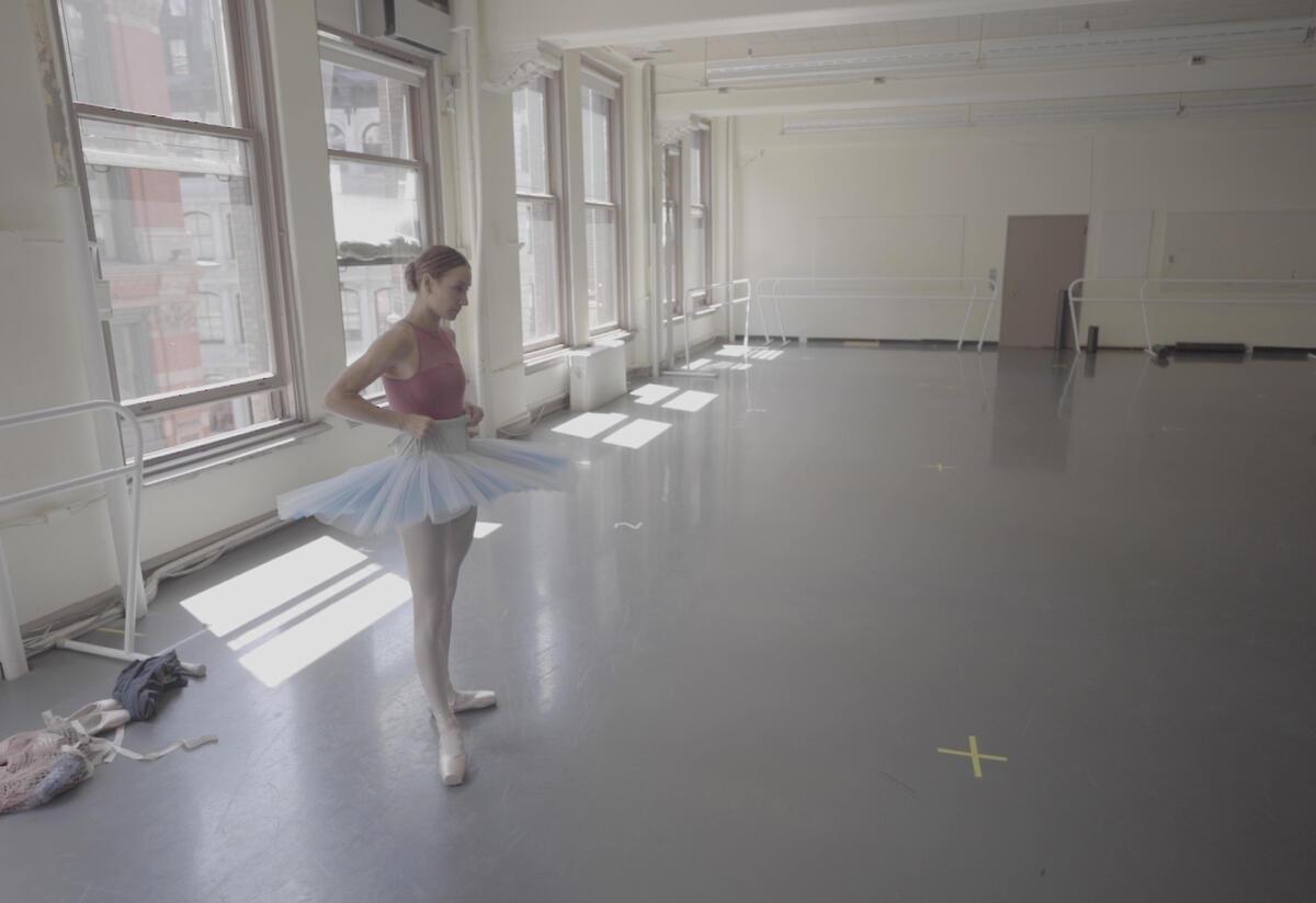 Ballerina Christine Shevchenko, wearing a tutu, stands poised to rehearse in a dance studio