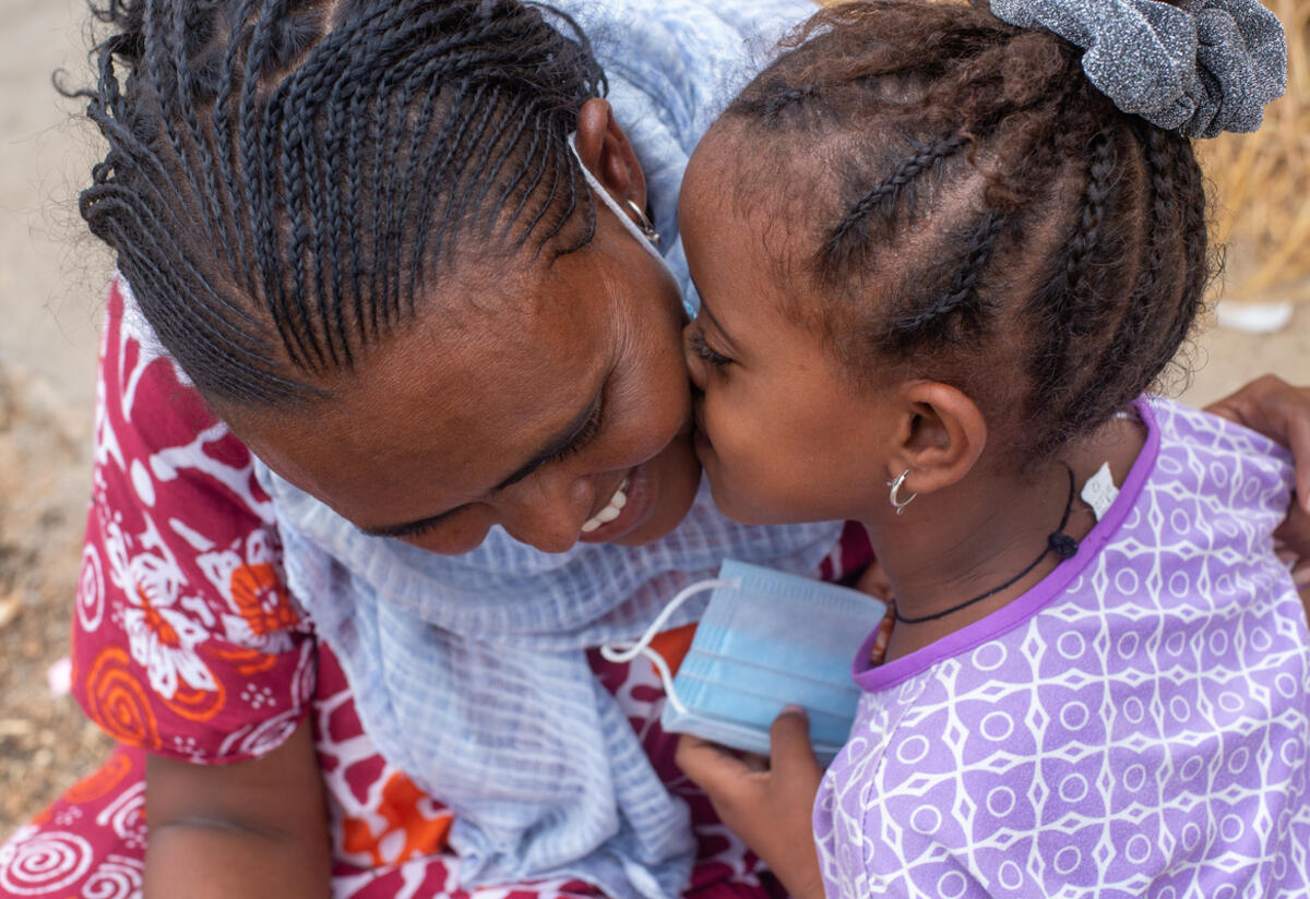 Azmera, 30, from Tigray, smiles as her young daughter kisses her cheek.