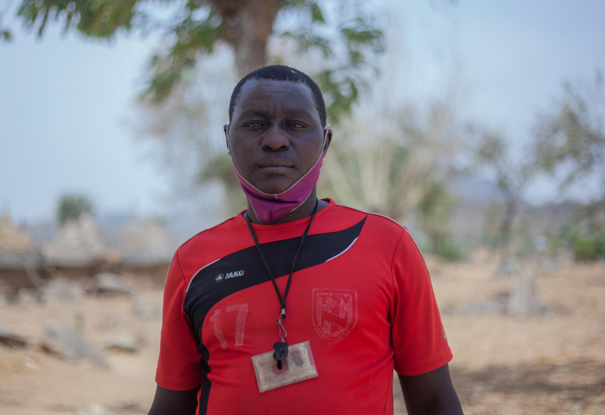 41-year old Komonda stands outside an IRC Safe Space in northern Cameroon, near a tree on a bright day.