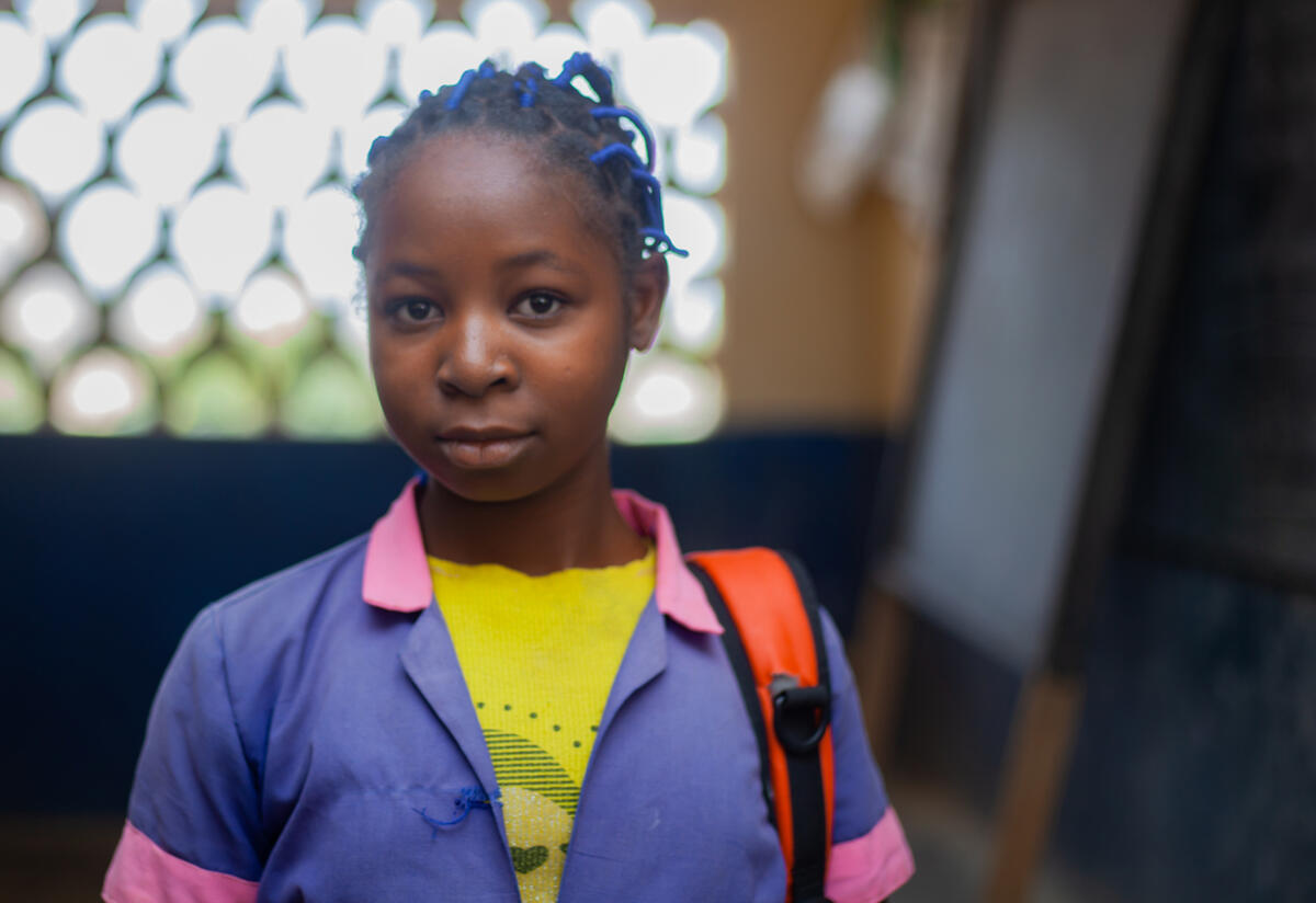 11-year old Kauvaumah stands in a classroom with her backpack slung over her shoulder.