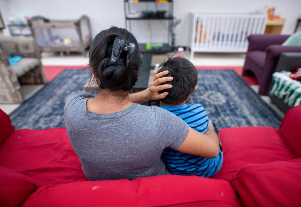 Angelina, una solicitante de asilo de Guatemala, se sienta en un sofá rojo con los brazos alrededor de su hijo en un Centro de Bienvenida del IRC en Arizona.